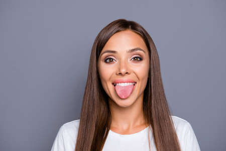 Close up portrait of funny young woman showing tongue.