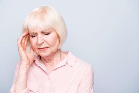 Portrait of old adult caucasian lady feeling head ache, pain.