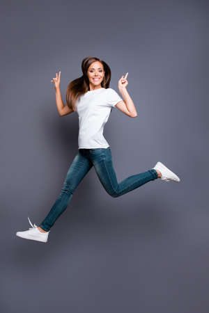 Full-body full-size portrait of cheerful girl who jumps and show Stock Photo