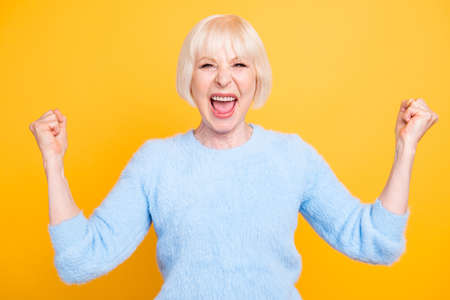 Close up portrait of  cheerful granny with toothy smile raised hand. Stock Photo