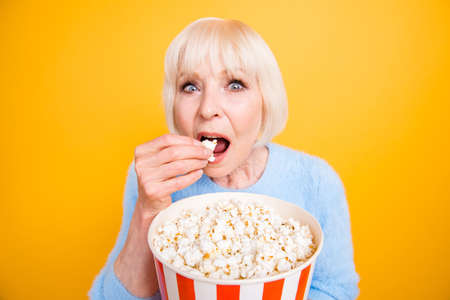 Old woman with holding a bucket of popcorn and watching exciting