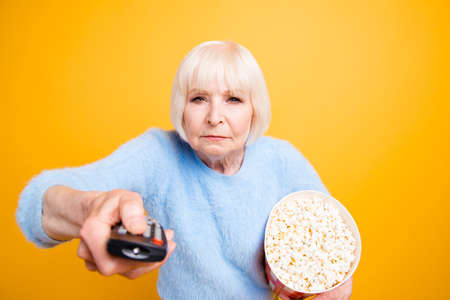 Concentrated old lady with bucket of popcorn switches channels o