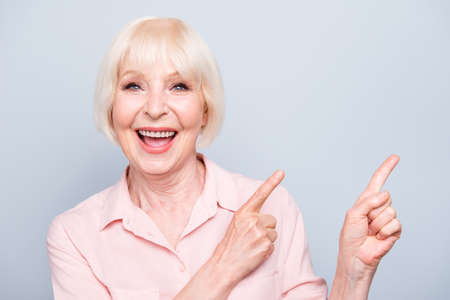Portrait of old blonde glad lady smiling, laughing, fingers poin