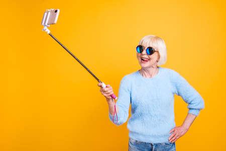 Abuela de alma joven haciendo selfie a la cámara frontal aislar Foto de archivo