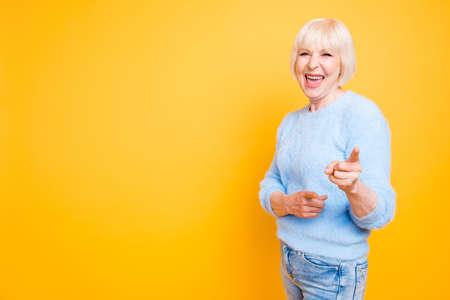 Porträt der selbstbewussten modernen Oma, die zwei Zeigefinger a zeigt