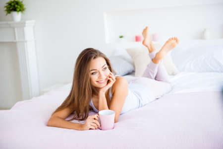Portrait of charming attractive girl lying on stomach in bed loo Stock Photo