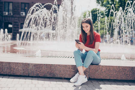 Full-size portrait of slim young girl sits near the fountain in Stock Photo