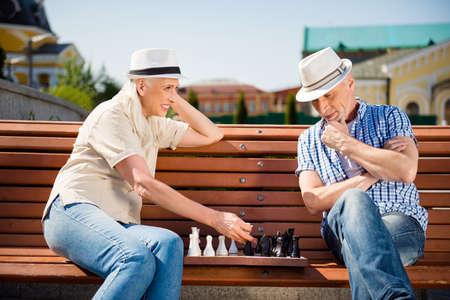 Portrait of playful beautiful grandma and granddad sitting on be