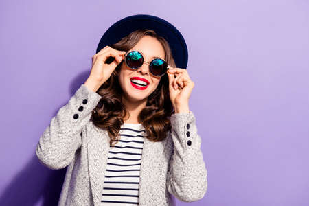 Portrait of funny carefree girl holding eyelets of glasses with