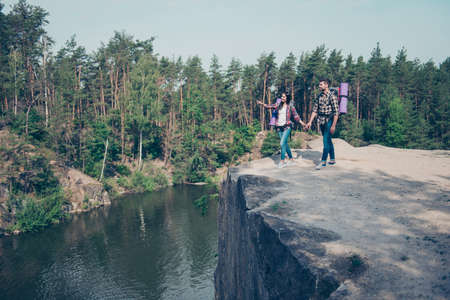 Two excited cheerful people with backpacks on top of rock stone Stock Photo - 107831523