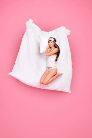 Full length size body young gorgeous smiling lady wearing eye mask, sleeping on pillow blanket and soft linen. Isolated over pink pastel background Stock Photo