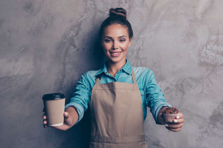Woman holding coffee and cupcake  against grey background 스톡 콘텐츠