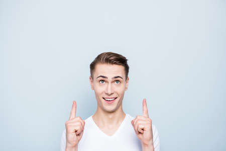 Portrait of cheerful, good-looking man look up, show aside by fi