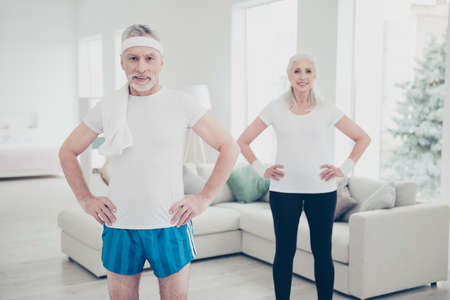 Two adorable healthy charming stylish old people doing physical
