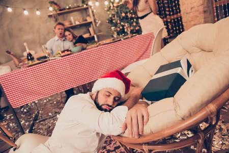 Bearded guy in santa claus cap sleeping on floor, chair near gif