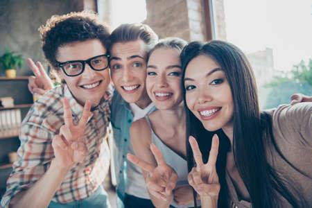 Autoportrait de quatre personnes adorables et joyeuses, de beaux mecs nerds et de belles filles attirantes se reposant, faisant une pause, montrant des signes v au travail, se rencontrant, se réunissant, diversité