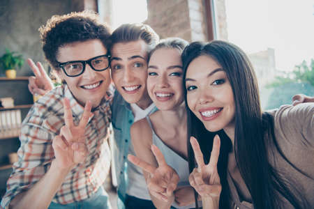 Self-portrait of four cheerful glad adorable people, handsome nerd guys and beautiful attractive girls having rest, pause, break, showing v-signs at work, meeting, gathering, diversity