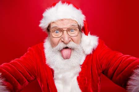 Close up aged face playful funky stylish grandfather Santa fooli Stock Photo