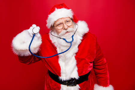 Worried calm Santa look at camera hold stethoscope in hand stand