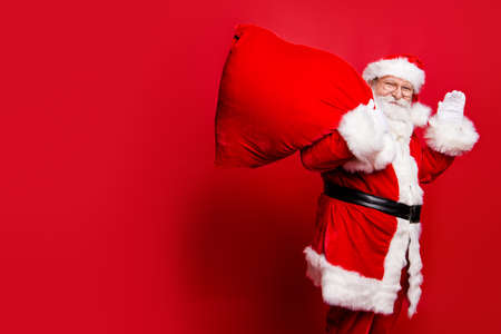 Cheerful nice peaceful Santa in eyeglasses wishes you merry Christmas