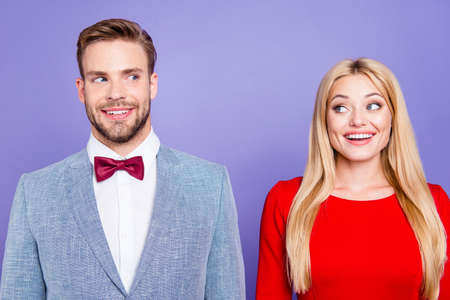 He and she so happy and dreamy Photo of handsome curious brunet man and blonde lady with straight hair look to each other in classy wear with bowtie isolated on bright purple violet background