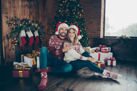 Two cheerful nice adorable people, married couple wearing santa