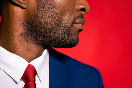 Cropped half face profile side view portrait of calm serious rich handsome well-groomed mulato man with perfect beard in blue suit isolated over red background