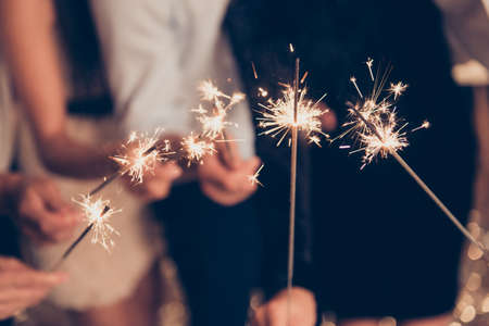 Foto ravvicinata ritagliata di bastoncini di fuoco del Bengala, scintillanti, brucianti, eleganti signore di classe e mani di signori che tengono insieme i bastoncini di fuoco, riunione, squadra, saluti, congratulazioni, buon Natale Archivio Fotografico