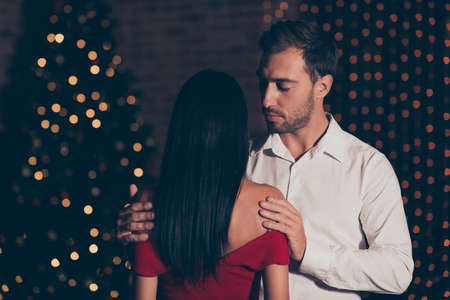Attractive, handsome man in formal wear hold brunette lady in re