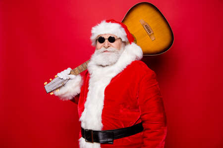 Handsome good-looking attractive Santa in winter gloves spectacles with white beard hold guitar on shoulder ready prepare playing song singing sound isolated on red shine background