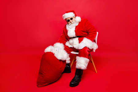 Winter Christmastime party over. Full legs body size confident calm serious Santa in shoes white gloves spectacles with beard sit on chair hold heavy sack by hand isolated on red shine background