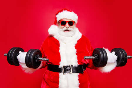 Portrait of stylish virile strong muscular sporty Saint Nicholas in eyeglasses gloves fur white red winter coat clothes holding lifting two big dumbbells in arms striving isolated on red background