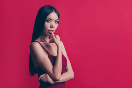 Profile side view well-groomed charming person she isolated on red maroon pastel background with copy space for text look at camera touch her low lip by finger 免版税图像