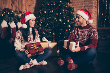 Full length legs body size portrait of two adorable people in jeans and socks hold big package with bow sit on floor in cozy, comfort living room with illumination garland on pine tree Banco de Imagens