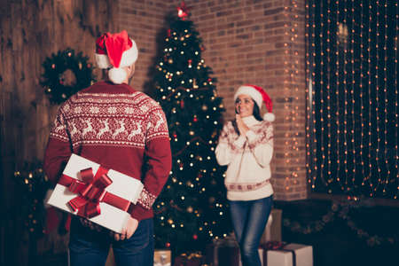 Handsome man in jeans, ornament sweater hide big package behind his back to surprise his girlfriend
