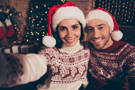 Winter christmastime concept. Handsome man and brunette beautiful, sweet, charming, attractive lady in ornament sweater stand in comfort, cozy house interior make selfie on front camera of smartphone
