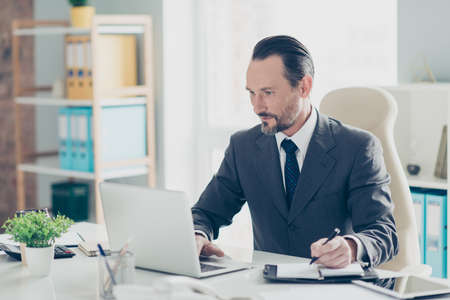 Portrait of accountant advocate agent expert man in stylish style tuxedo formalwear using pc gadget look on monitor make calm face note important information sit on chair armchair Foto de archivo - 150049564