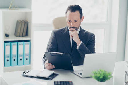 Attractive handsome calm face brunet hair analyst man in formal wear sit on chair armchair behind table in bright lite office hold important document and read it attentively Foto de archivo