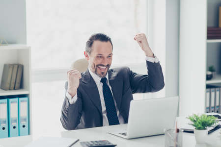 Half turn glad realtor sale manager secretary stylish style trendy man in formal wear look on technology modern notebook screen monitor raised hands fists up sit on chair armchair in workstation