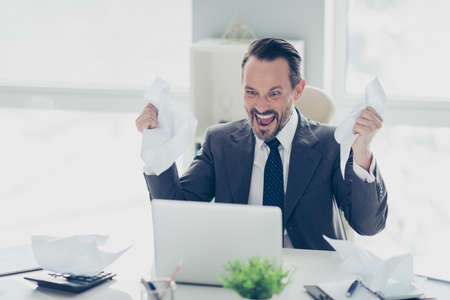 Aggression face analyst banker broker ceo man in formal wear look on modern technology monitor sit on chair armchair behind desktop in white cabinet hold document in hands Foto de archivo - 150049824