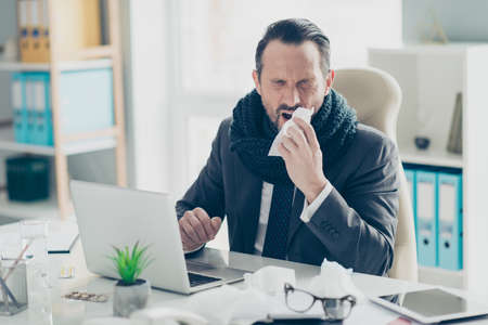Director executive financier lawyer entrepreneur man classy formal wear stylish tuxedo sit on chair armchair behind desktop with modern technology on workplace close eyes hold napkin near face Foto de archivo - 150049845