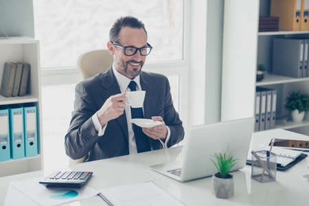 Attractive handsome dreamy man in trendy style stylish tux formal wear look on modern technology screen monitor sit on armchair behind desktop in bright lite workplace office hold beverage in hands Foto de archivo - 150050002