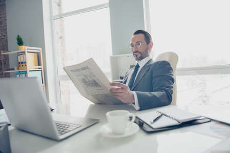 Confident attractive handsome good-looking man in elegant classy formal wear sit on comfort white armchair chair behind desktop in bright lite office reading important information