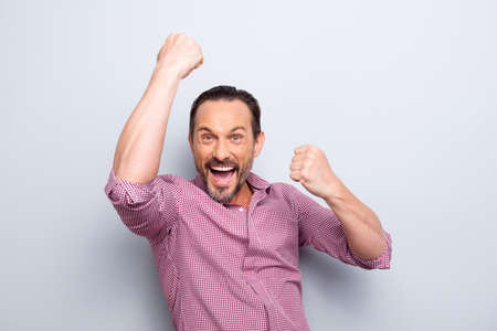 Human emotion reaction concept. Portrait of attractive good-wearing cheerful careless carefree man raised fists hands up isolated on light gray background make wide open mouth