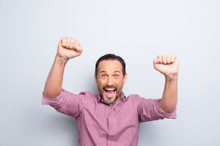 Portrait of handsome cheerful glad attractive man in casual checkered raised fists up isolated on light gray background look at camera with wide open mouth beaming toothy smile