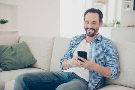 Hombre de cabello brunet despreocupado descuidado sonriendo optimista en cuadros