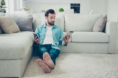 Hombre barbudo de pelo castaño de tamaño corporal de piernas completas mantenga gadget en las manos