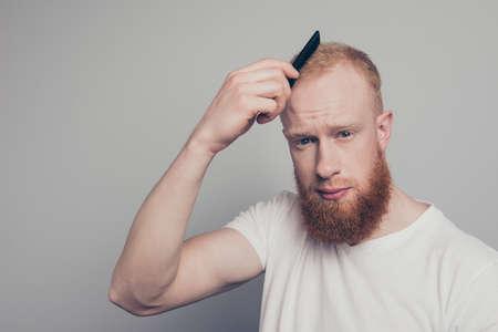 Charming good-looking gentleman combing hair look at camera
