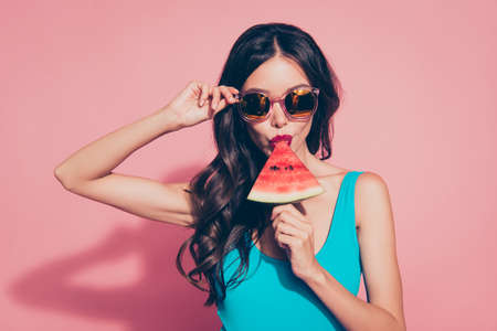 Close-up portrait of cool stylish trendy naughty cheeky adorable charming attractive gorgeous wavy-haired lady biting melon piece eyeglasses eyewear isolated over pink background