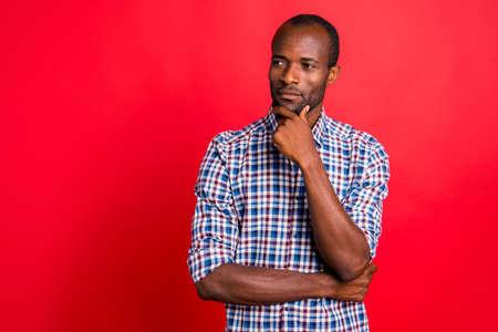 Porträt eines hübschen, gut aussehenden, attraktiven, ruhigen Kerls, der ein kariertes Hemd trägt, das das Kinn berührt, einzeln auf hell leuchtendem, rotem Hintergrund